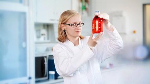 Junge Wissenschaftlerin mit Brille hält eine Flasche mit roter Flüssigkeit in den Händen und betrachtet sie.