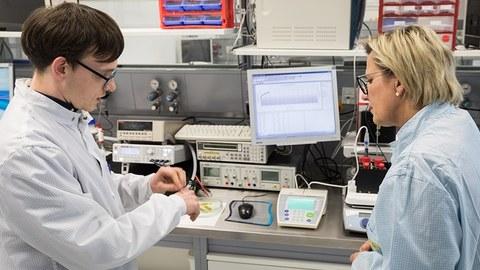 Das Foto zeigt Frau Staatsministerin Klepsch (rechts im Bild), die sich in den Laboren im Werner-Hartmann-Bau über das Projekt FlexEO informiert. Links im Bild sieht man einen jungen Mann, der der Staatsministerin etwas erklärt.