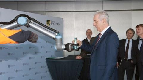 Auf dem Foto sieht man den ehemaligen Ministerpräsidenten Stanislaw Tillich während der Pressekonferenz zum Smart Systems Hub Dresden, wie er von einem Roboterarm eine Flasche Wasser entgegennimmt.