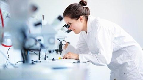 Auf dem Foto sieht man eine junge Wissenschaftlerin im weißen Kittel, die durch ein Mikroskop schaut.