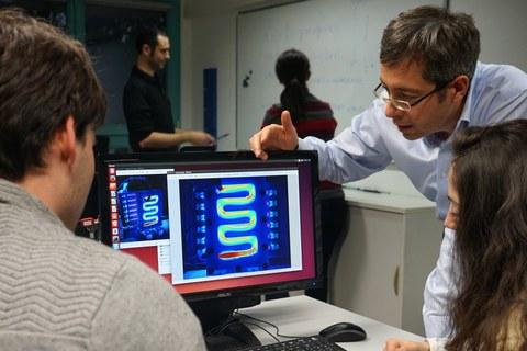 Zwei Personen sitzen vor einem Bildschirm, auf dem eine Simulation abgebildet ist. Rechts sieht man einen Mann, der etwas dazu erklärt.