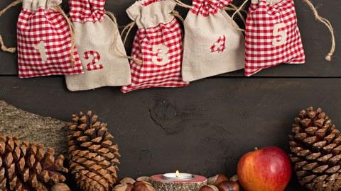Auf dem Bild sieht man in der oberen Hälfte fünf Jute-Säckchen eines Adventskalenders. Darunter sind Tannenzapfen, Haselnüsse, ein Teelicht und ein Apfel abgebildet.