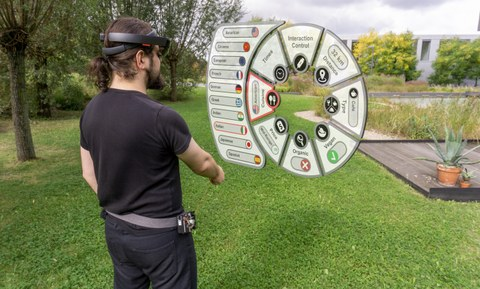 The picture shows a collage of photo and 3D visualization. A man stands on a meadow with 3D glasses and looks virtually at a special user interface.