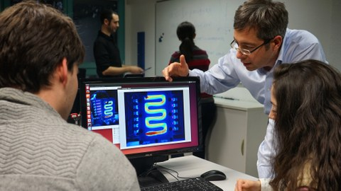 The photo shows the materials scientist Prof. Gianaurelio Cuniberti (2nd from right) explaining something to two people on a computer screen.