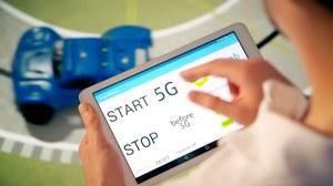 Auf dem Foto sieht man einen jungen Mann, der über ein Touchpad ein Miniaturauto auf einer Testrennstrecke mit 5G bedient.
