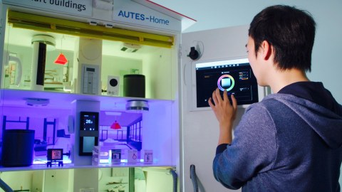 The photo shows a man operating a model of a smarthome via a touch panel.