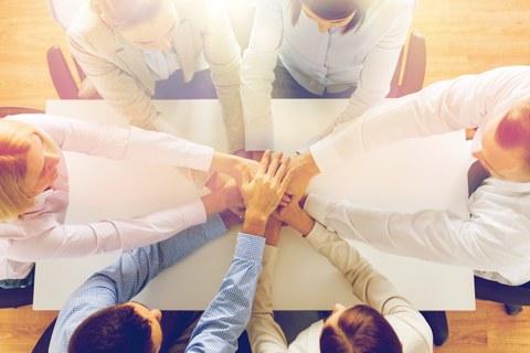 Nahaufnahme am Tisch von einem Team. Sitzen und halten die Hände auf der jeweils anderen.