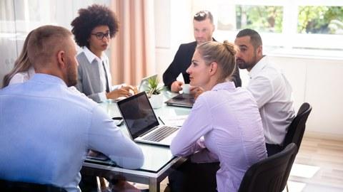 Gruppe von Geschäftsleuten, die während des Geschäftstreffens im Büro sitzen.