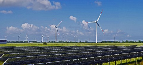 On the photo you can see a landscape with a solar park consisting of wind turbines and solar panels.
