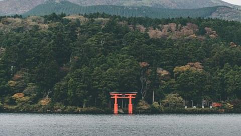 Das Foto zeigt eine Landschaft mit einem See im Vordergrund. Im Hintegrrund sieht man Berge und am Ufer eine Art Tor.
