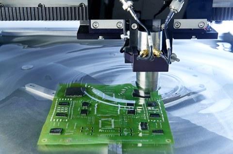 Im Wasser liegt eine grüne Leiterplatte. Diese wird mit Hilfe des Sonoscans, einem technischen Gerät, auf Schäden untersucht. Dabei fährt der Scanner im Wasser über die Leiterplatte.