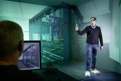Ein junger Mann steht in einen Raum zur Projektion einer dreidimensionalen Illusionswelt der virtuellen Realität. Er hat eine Datenbrille auf und einen Controler in der Hand. Im Vordergrund sitzt ein Mitarbeiter vor einem Computer.