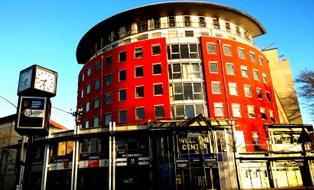 Das Foto zeigt ein Gebäude am Nürnberger Ei. Es ist rund gestaltet mit roter Fassade.