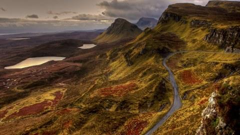 Auf dem Foto sieht man eine Straße, die sich durch eine Gebirgslandschaft schlängelt.