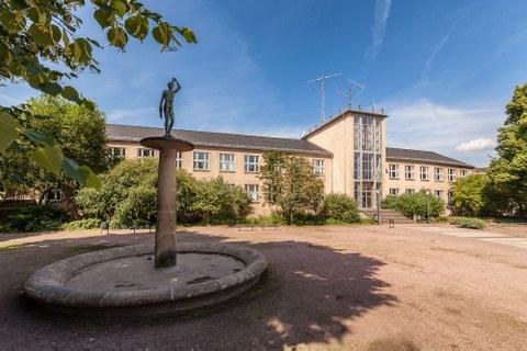 Das Foto zeigt den Blick auf den Barkhausen-Bau der TU Dresden. Im Vordergrund links sieht man den Brunnen, der auf der Freifläche vor dem Barkhausen-Bau steht.