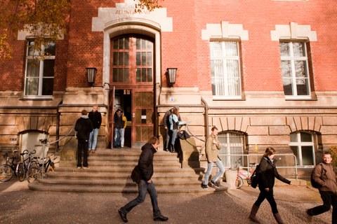 Auf dem Foto sieht man den Haupteingang des Zeuner-Baus. Studierende verlassen das Gebäude.