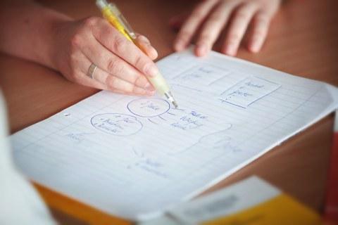 Auf dem Foto sieht man die Hände einer Frau, die auf einem Blatt Papier etwas skizziert.