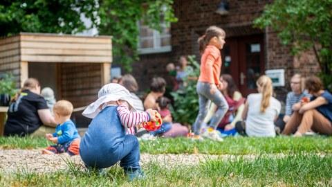 Foto eines Kleinkindes, das mit dem Rücken zum Betrachter auf einer Wiese hockt und einen Greifball hält. Im Hintergrund sind weitere Kinder mit ihren Eltern, Gebäude, Bäume und Wiese zu sehen.