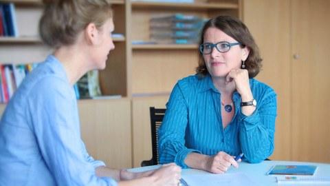Auf dem Foto sieht man eine junge Studentin mit einer Kollegin aus der Studienberatung am Tisch sitzen.