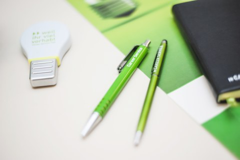 "Two pens and one highlighter marked with the inscription ""Career Service"" beside a black notebook"