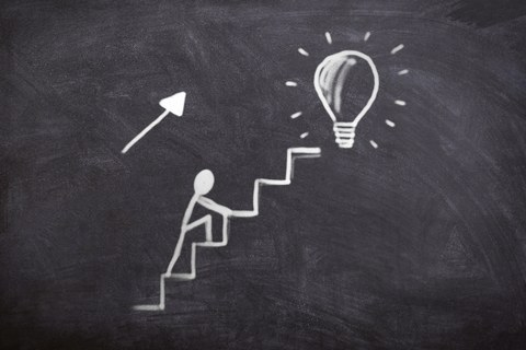 Drawing on a blackboard showing stickman climbing up stairs. At the end of the stairs is a light bulb.