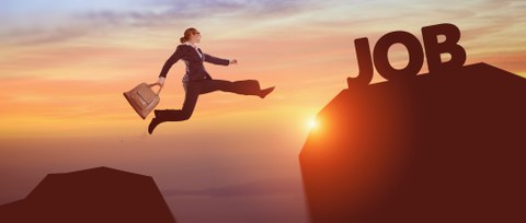 """Woman in a business outfit and with a briefcase jumping from one big rock to another. On her destination rock it reads """"JOB""""."""