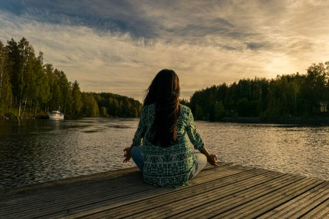 Meditating woman sitting on a dock in front of a lake