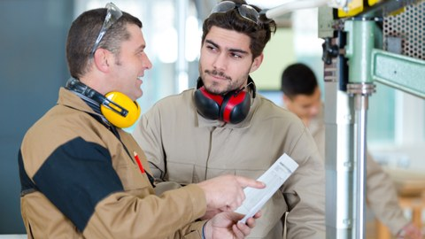 two men with hearing protection, standing in front of technical machines, the older man explains something