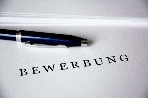 """sheet of paper with the title """"Bewerbung"""" (german for application) and a pen next to it"""