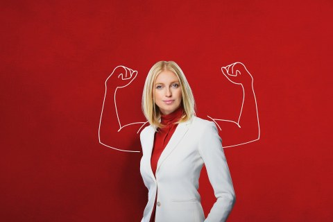 Woman standing in front of a red background. On this background muscular arms are drawn.