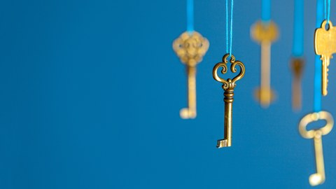 Many old keys of yellow gold color are hanging on thread on a blue background. The concept of the selection of access or password to the secret data.