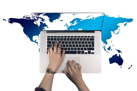 Top view of a laptop with hands on the keyboard. The desktop shows a section of a Eurocentric world map. This section is continued in the background, around the laptop.
