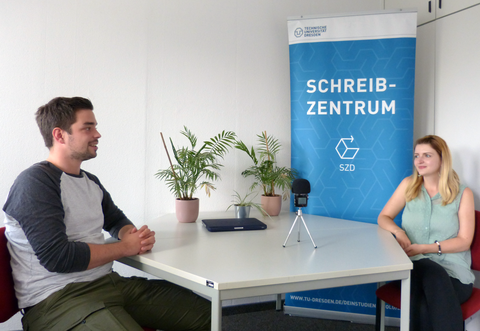 The photo shows two people smiling at each other, sitting at a table in front of an audio recording device. On the table are three green plants, behind them a banner with the logos and lettering of the Writing Centre and the TU Dresden.