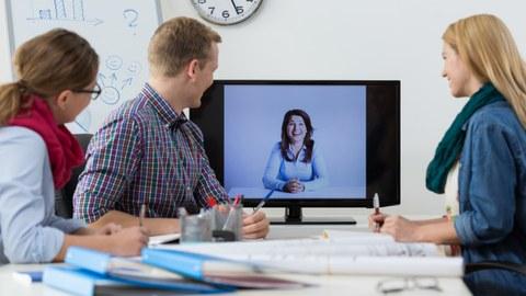 Foto: Drei Personen sitzen um einen Tisch und blicken in einen Bildschirm. Auf dem Bildschirm ist eine Frau zu sehen, die lacht. Vermutlich machen die Personen eine Videokonferenz.