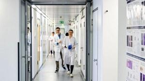 Zwei Wissenschaflter laufen durch Laborflur
