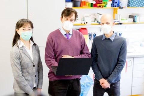 Drei Menschen stehen mit Mund-Nasen-Bedeckung vor einem Rednerpult.