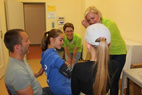 Besucher messen sich unter Anleitung selbst den Blutdruck