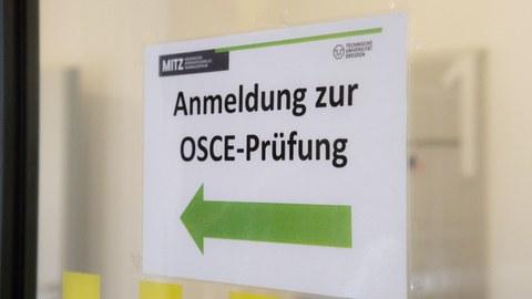 """Schild mit grüner Schrift und Aufdruck """"Anmeldung zur OSCE-Prüfung"""""""