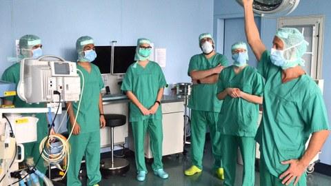 Medizinstudierende werden von einem Arzt die mediziischen Geräte eines OP Saals gezeigt