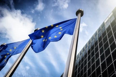 Zwei Flaggen der Europäischen Union vor einem Gebäude.