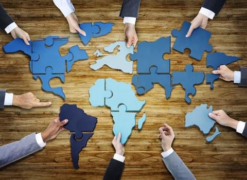 Hände bauen eine Weltkarte aus Puzzleteilen zusammen