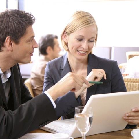 Eine Frau im Blazer schaut gemeinsam mit einem Mann auf den Bildschirm eines Laptops