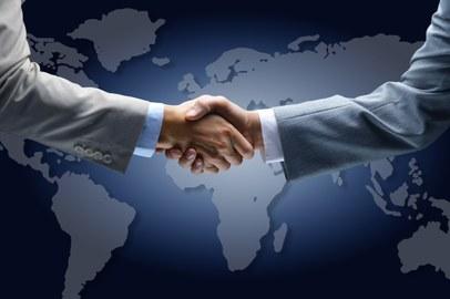 Zwei Menschen im Anzug schütteln sich vor dem Hintergrund einer Weltkarte die Hände