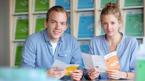 Zwei Studierende mit Informationsblättern für Studiengänge