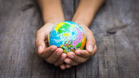 Das Foto zeigt die Hände einer Person. Die Hände bilden eine Schale. In der Schale liegt eine kleine Weltkugel.