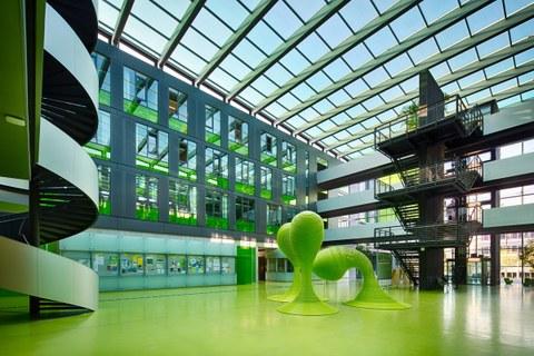 Blick in das Foyer des Andreas-Pfitzmann-Baus der TU Dresden. Der Boden des Foyers ist grün. In der Mitte stehen drei grüne Skulpturen