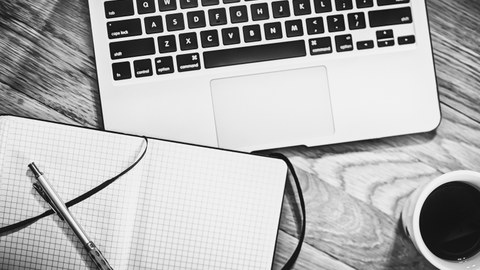 Laptop, Notizbuch und Kaffee