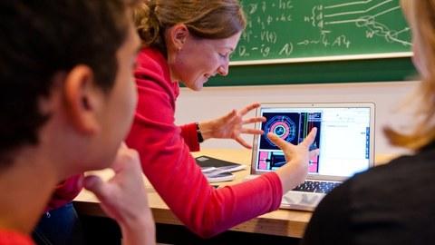 Schüler und Tutorin betrachten ein ATLAS event display