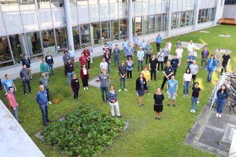 Wissenschaftliche Teilnehmer des Konferenz des SFB 1143 im Jahr 2021 auf einer Wiese, fotografiert von oben.
