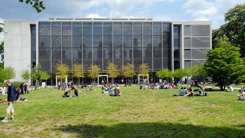 Rückseite des Hörsaalzentrum der TU Dresden. Auf der Wiese sitzen viele Studierende in kleinen Gruppen.